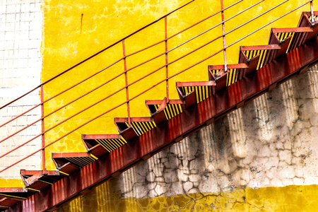 Red metal stair along the yellow wall Archivio Fotografico
