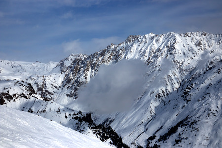 View of the snow-covered mountain. Cloud lies on the slope of the mountain