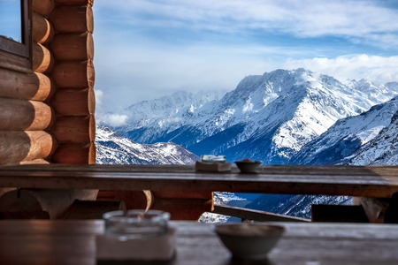 View of the Main Caucasian ridge. Defocused wooden tables of mountain cafe in the foreground
