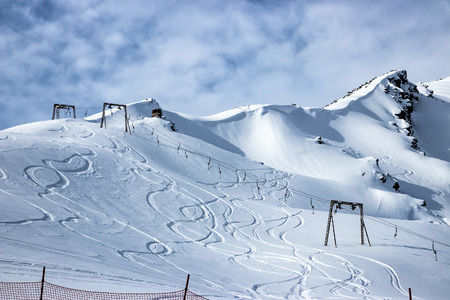 View of the snow-covered mountain range. Ski tracks on the mountainside and chairlift