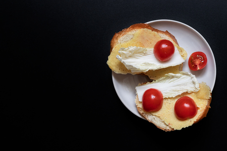 Toasted bread with lettuce and cherry tomatoes on black background. Top view 版權商用圖片