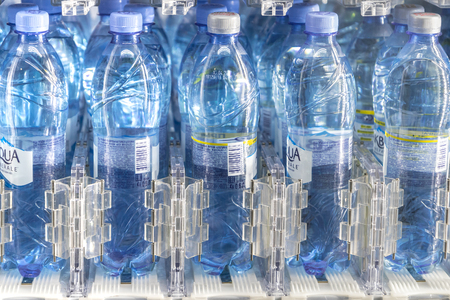 Moscow, RUSSIA - April 12, 2019: rows of water bottles of the Aqua Minerale trademark. Plastic bottle holders in vending machine 新聞圖片