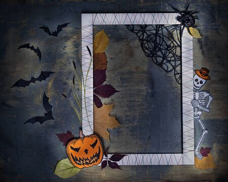 Photo frame with paper models of Pumpking Jack, skeleton Zombie, bats and spider on old shabby background. Halloween holiday concept, flat lay, space for text