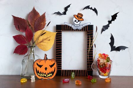 Funny composition with empty photo frame for Halloween holiday. Skeleton Zombie, Jack o Lantern, bats, mug with candy, vase with dry autumn leaves on wooden table. Mock up, space for text 版權商用圖片