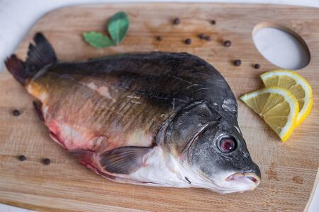 Raw mirror carp with peppers and lemon on cutting board. Cooking fish. Focus on foreground Фото со стока