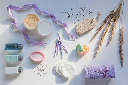 Natural cosmetic and bath products on white background in sunlight rays. Dry lavender flowers and wild cereal grass. Concept of face and body skincare at home, spa or wellness center. Flat lay composition
