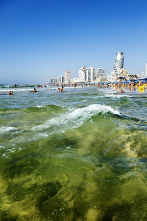 Tel-Aviv, Israel - September 3rd, 2011: View looking north at the Tel-Aviv shoreline and hotels strip on a clear day; with its long beach packed with thousands of people bathing either in the sun or in the warm Mediterranean waters.