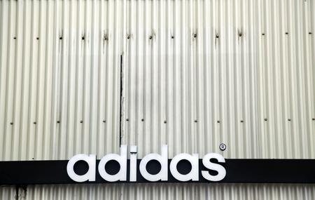 adidas: Tel-Aviv, Israël - 10 maart 2011: De Adidas handelsmerk merknaam op de achtergrond van kronkelende metalen. Adidas is de grootste fabrikant van sportkleding in Europa en de tweede grootste fabrikant van sportkleding in de wereld. Redactioneel