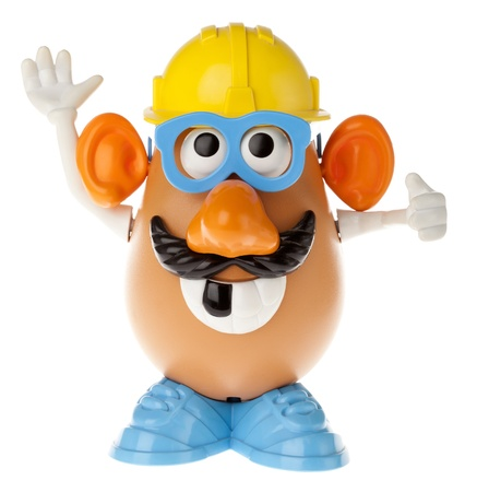 toy story: Tel-Aviv, Israel - January 25th, 2012: Isolated on white studio shot of the famous toy Mr. Potato Head, by the Hasbro company. He is wearing a mustache, glasses and a yellow workman hard-hat; a large missing-tooth smile and gesturing with his hands as if  Editorial