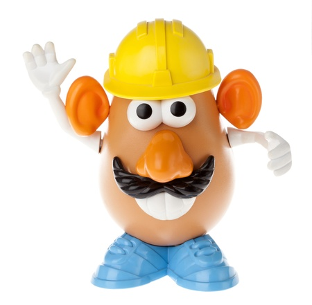 mr: Tel-Aviv, Israel - January 25th, 2012: Isolated on white studio shot of the famous toy Mr. Potato Head, by the Hasbro company. He is wearing a mustache and a yellow workman hard-hat, a large toothy smile and gesturing with his hands as if directing the mo Editorial
