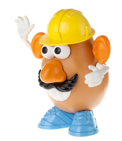 mococa: Tel-Aviv, Israel - January 25th, 2012: Isolated on white studio shot of the famous toy Mr. Potato Head, by the Hasbro company. He is wearing a mustache and a yellow workman hard-hat, a large toothy smile and gesturing with his hands as if directing the mo Editorial