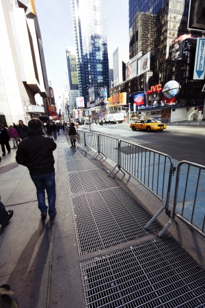 yellow taxi: New-York, USA - November 6th, 2012: Pedestrians waiting on the sidewalk while a yellow taxi rushes down the street at Times Square in Manhattan at autumn noon. Editorial