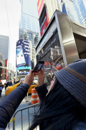 commotion: New-York, USA - November 6th, 2012: An adult Caucasian woman in her 30s using her smartphone to take photos in times square, Manhattan, on a sunny autumn day, with all the regular commotion around. Editorial