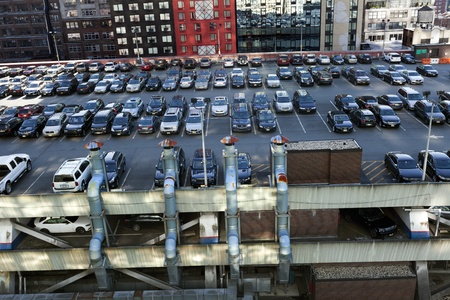 car parking: New-York, USA - November 6th, 2012: Wide angle view of the NYC Port Authoritys (central bus station) rooftop parking lot, almost full with cars, and surrounded by midtown skyscrapers. Editorial