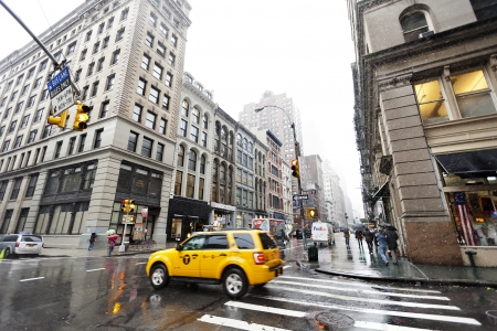 New-York, USA - November 7th, 2012: A yellow taxi is waiting for the rushing pedestrians crossing the street on the corner of Broadway and Walker st., located in Chinatown, Manhattan, on a rainy day.