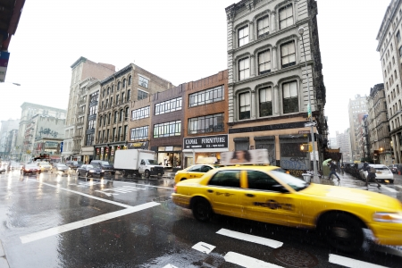 New-York, USA - November 7th, 2012: Two yellow taxis advancing downtown on Broadway, in the Chinatown area, on a rainy winter day.