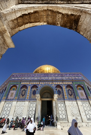 holiest: Jerusalem, Israel - May 9th, 2012: Groups of tourists and Muslim pilgrims visiting one of the holiest places to the Islam, the Dome Of The Rock in the old city of Jerusalem. Seen from within one of the arches leading to the mosque. Editorial