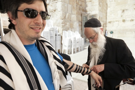 phylacteries: Jerusalem, Israel - May 9th, 2012: An adult Caucasian man wearing a praying shawl , while being helped by a Rabbi with putting on the Phylacteries (Teffilin, Tefilin, Tfilin). This man is a Jewish tourist visiting the holy Western Wall (aka Wailing Wall)