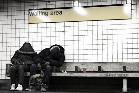 designated: New-York, USA - November 14th, 2012: Two anonymous ault people sitting on a bench at a subway stations designated waiting area, hidden behind their coats, appear to be sleeping. Editorial