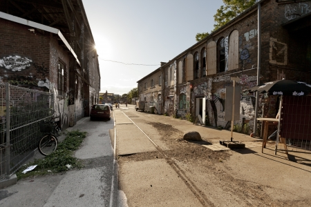 run down: Berlin, Germany - June 9th, 2012: A view at the Raw tempel area main road, with grafitti covered buildings on both sides, located in Friedrichshain. Once an industrial park, these days this area is full with leisure activities on the weekends, attracting