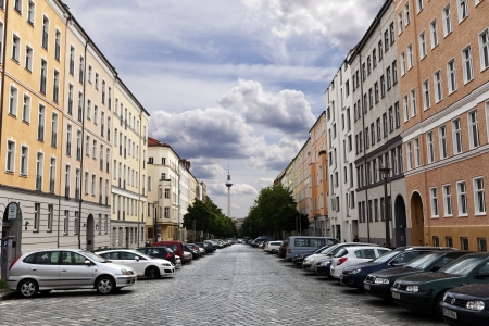 Berlin, Germany - June 10th, 2012: Diminishing perspective view of the blocks of buildings that stretch along Strelitzer strasse with a large amount of cars parking beneath them. In the distance - the Berlin Television Tower (Fernsehturm) beneath blue clo