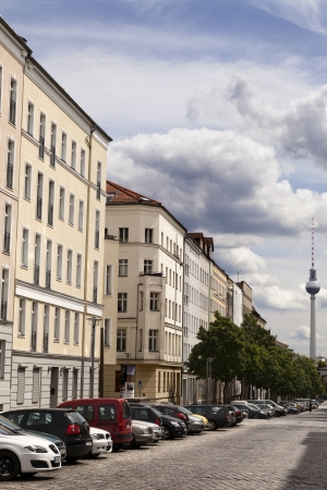 diminishing perspective: Berlin, Germany - June 10th, 2012: Diminishing perspective view of the blocks of buildings that stretch along Strelitzer strasse with a large amount of cars parking beneath them. In the distance - the Berlin Television Tower (Fernsehturm) beneath blue clo