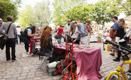 sunday market: Berlin, Germany - June 10th, 2012: Large amount of people walking in the Sunday flee market held at Mauer Park. Homemade knives are displayed for sale in the foreground table.