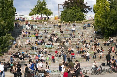 Berlin, Germany - June 10th, 2012: Early summer Sunday afternoon at the Mauerpark amphitheater. Manu people are sitting on the stone terraces, and many others are socializing and walking by it.