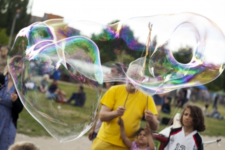 optimisim: Berlin, Germany - June 10th, 2012: A group of  childern and adults making giant soap bubbles on an early summer Sunday afternoon at Mauerpark, with the flea market in the background. Editorial