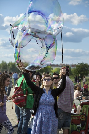 optimisim: Berlin, Germany - June 10th, 2012: A young adult woman making giant soap bubbles on an early summer Sunday afternoon at Mauerpark, with the parks crowd all around and flea market in the background.