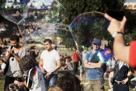 optimisim: Berlin, Germany - June 10th, 2012: The crowd at Mauerpark seen through giant soap bubbles on an early summer Sunday afternoon. Editorial