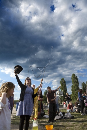 spectating: Berlin, Germany - June 10th, 2012: A group of people making giant soap bubbles on an early summer Sunday afternoon at Mauerpark, with the parks crowd scattered around them, some spectating. The woman at the front is raising a hat with her hand, requestin