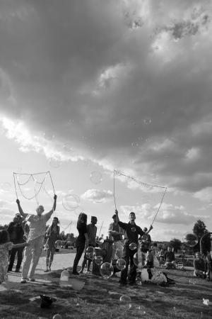 spectating: Berlin, Germany - June 10th, 2012: A group of people making giant soap bubbles on an early summer Sunday afternoon at Mauerpark, with the parks crowd scattered around them, some spectating.
