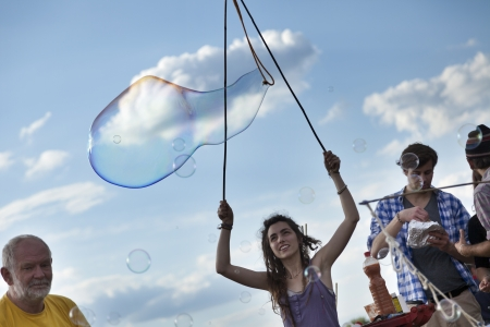 optimisim: Berlin, Germany - June 10th, 2012: A group of people making giant soap bubbles on an early summer Sunday afternoon at Mauerpark.