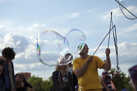 optimisim: Berlin, Germany - June 10th, 2012: A mature man making giant soap bubbles on an early summer Sunday afternoon at Mauerpark, with the parks crowd all around.