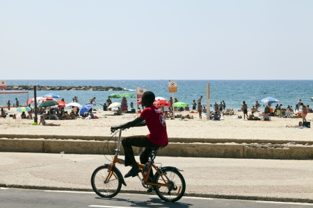 east riding: Tel-Aviv, Israel - August 18th, 2012: A young man riding his bicycle on the boardwalk along the packed Tel-Aviv beach. Editorial