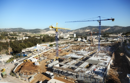 Beit-Shemesh, Israel - December 28th, 2011: High & wide angle view of a shopping mall construction site located in Beit-Shemesh's western industrial park; surrounded by beautiful green hills scenery on a clear day. It appears that the construction some of Stock Photo - 18899659