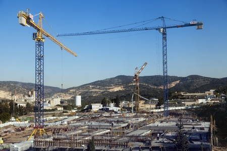 industrial park: Beit-Shemesh, Israel - December 28th, 2011: High angle view of a shopping mall construction site located in Beit-Shemeshs western industrial park; surrounded by beautiful green hills scenery on a clear day. It appears that some of the construction worker