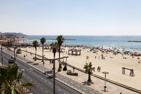 Tel-Aviv, Israel - August 18th, 2012: High angle view to the south-west, of the beach and boardwalk in Tel-Aviv, packed with people on a hot summer day. Cars are driving on the street along the boardwalk, and cyclers are riding on the bicycle path on the