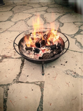 A pile of wood trunks burning in a contained fire. Image stylized with lo-fi washed-out vignette retro lomography toy camera aesthetics. Stock Photo - 18907705