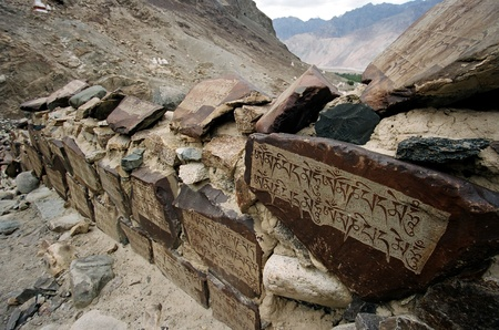 sanskrit: Mountain route in Nubra Valley (Ladakh, India) with wall paved with stones with religious writings on them. Stock Photo