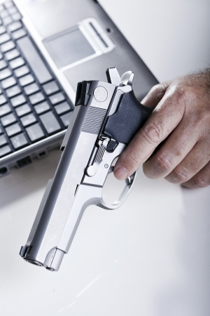 backlit keyboard: The left hand of a mature adult man holding a 9mm handgun, and a defocused laptop computer in the background. Backlit. Shallow depth of field.