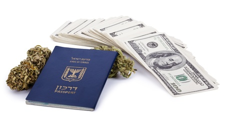 An Israeli passport, two Marijuana buds and a large stack of 100 US dollar money notes isolated on white background. photo