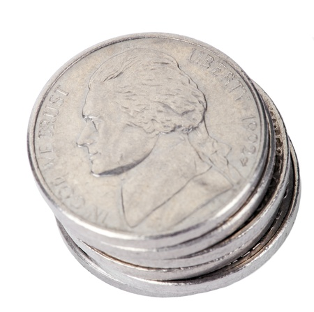 high angle shot: A high angle shot of a stack of 5 US cents (Nickel) coins isolated on white background. The obverse side of the coin is seen here, depicting Thomas Jeffersons profile portrait.
