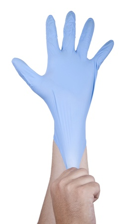 A young adult mans right hand stretching a disposable blue latex glove on his left hand. Isolated on white background. photo