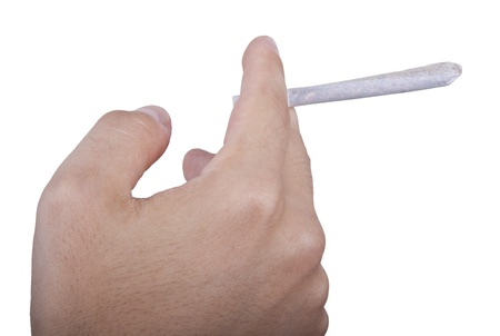 Closeup on the hand of a young adult man with an unlit reefer (joint, spliff...) held between his fingers. Isolated on white background. Stock Photo - 18920752