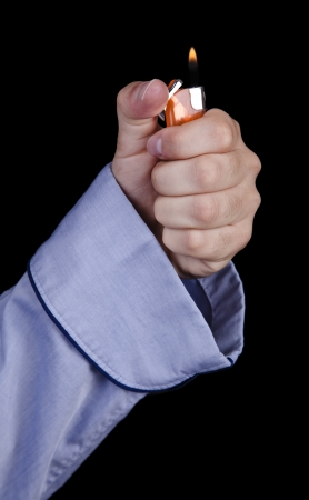 A young adult caucasian mans hand coming out of the sleeve of a blueazul cotton robe, igniting a simple disposable plastic orange lighter. Isolated on black background. photo