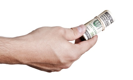 Close up of the right hand of an adult man holding a rolled up cluster of 100 US$ money notes wrapped in a rubber band, in the gesture of giving. Isolated on white background. photo