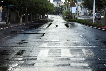 Early winter morning in Tel-Aviv, the wet street is empty from vehicles and people. photo