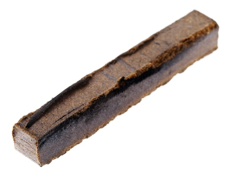 grams: A 10 grams piece of Hashish isolated on white background. This piece represents the shape and weight of a single retail unit.